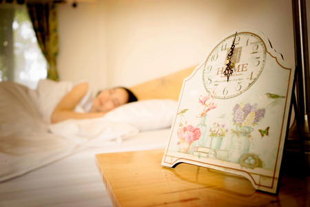 tiredness: Young woman sleeping in bed with alarm at night