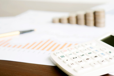 Selective focus calculator, pencil , coin on chart document.