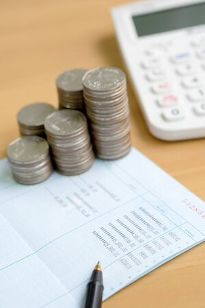 Coins stack in columns with saving book finance and banking concept for background