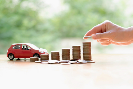 Businesswoman hand pushing a toy car over a stack of coins