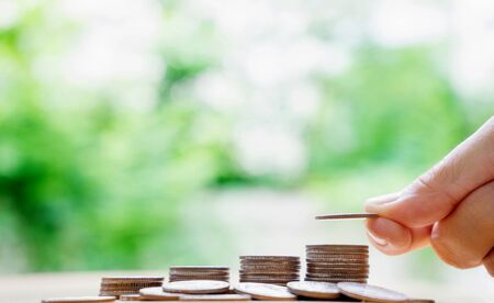 single word: hand put money coins to stack of coins. Money, Financial, Business Growth concept.