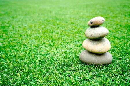 stones stacked up on grass