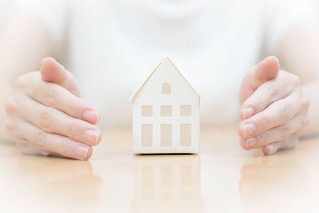 Female hands saving Miniature House Stock Photo