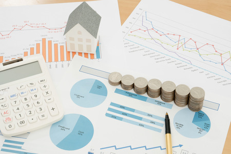 With House Model And Stack Of Coins On Desk Stock Photo