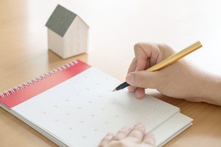Hand holding pen and marking on calendar Stock Photo