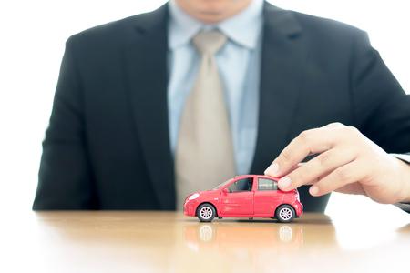 Businessman by a desk holding a toy car.