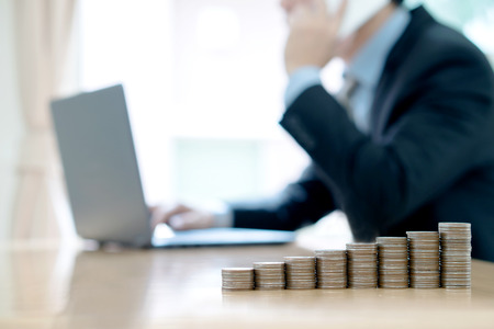 Coin stack step on desk with man using the computer