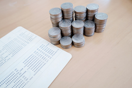 Saving money with coin stack and passbook on wood table