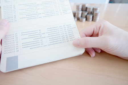 Woman hold passbook on hand, coins background Фото со стока