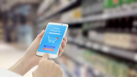 Woman using smart phon while shopping in supermarket Stock Photo