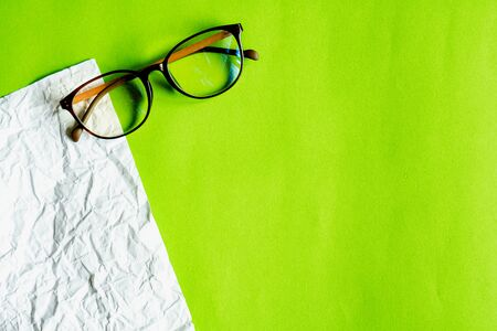 White crumpled paper and green paper. eyeglass concept. Stockfoto