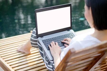 Frau, die mit Laptop arbeitet, sitzt am Swimmingpool