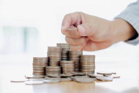 Ręka dająca monety do koncepcji stosu, biznesu i finansów
