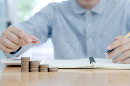 Business accounting with saving money with hand putting coins on stack concept financial