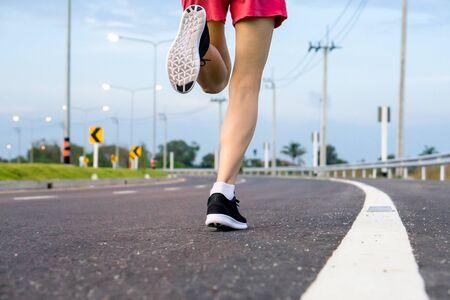 Movement. Woman legs running on asphalt road.  版權商用圖片