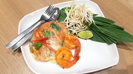 Thai noodle dish Pad Thai with prawns and omelet