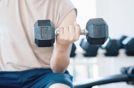 Man doing concentration curls exercise working out with dumbbell
