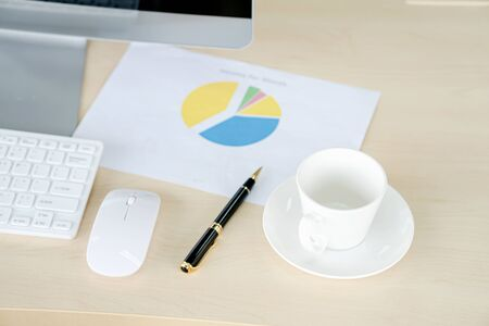 Business and workplace concept. Cup of hot coffee on work desk with computer keyboard and papers graphs