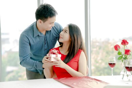 Man giving his girlfriend gift box with red ribbon