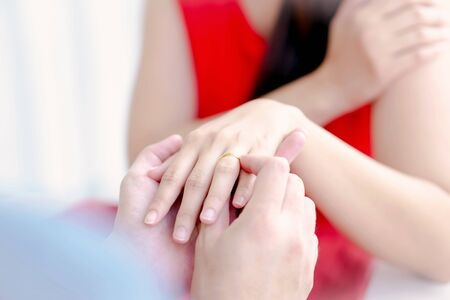 Close up of man putting wedding ring on woman finger