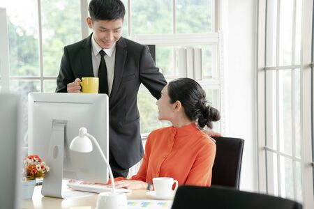 Two business people in the workplace working together. and discussing a project.