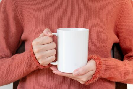 Woman in warm sweater is holding white mug in hands