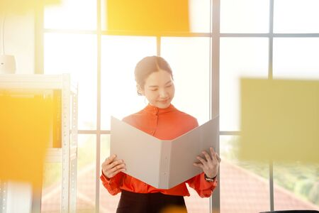 A Business woman is reading documents view through window Stock Photo