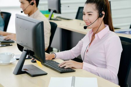 Shot of a happy call center agent working at her computer in the office