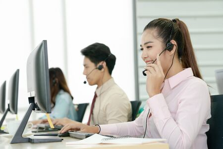 Positive female customer services agent with headset in call center