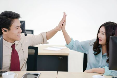 Call center team workers giving high five to each other at office