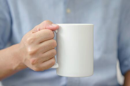 Businessman in warm sweater is holding white mug in hands
