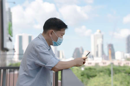 Young caucasian man mask holding smartphone for business work