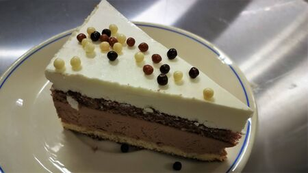 A piece of cake is served on a plate. The concept of bakeries, confectioneries, restaurants, cafes