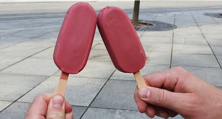 two ice creams on a stick with ruby chocolate in hand