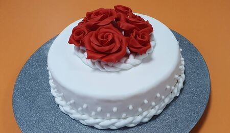 The cake is covered with white sugarpaste and decorated with red roses