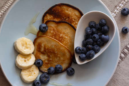 The pancakes on the plate are decorated with bananas, honey and blueberries, food and drink concept