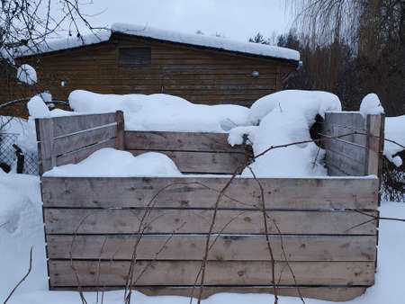 Wood compost bin in winter, food waste composted. Lets protect nature concept, ecological composting of food and garden waste, safe the planet concept