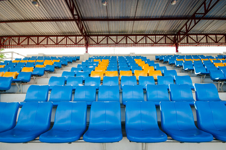 grandstand: Empty plastic chairs of blue and yellow  on grandstand stadium Stock Photo
