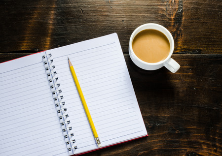 space to write: notebook pen and cup of coffee in wood table