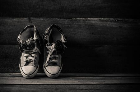 Sneakers on floor on wooden background,the black-white photo
