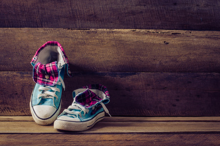 Sneakers on floor on wooden background photo