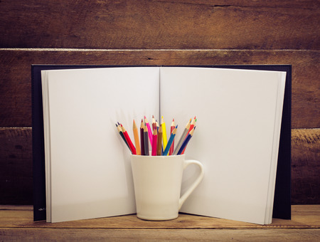 sketchbook: Color pencil and sketchbook on wooden background