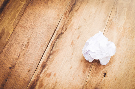 wastrel: crumpled paper ball on wooden background