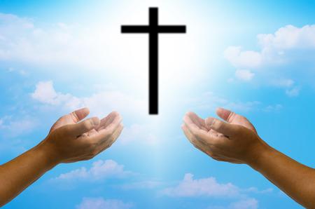 manos abiertas orando la cruz en el cielo de fondo borroso.