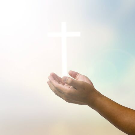 outstretched hand: open hands praying the cross on blur sky background