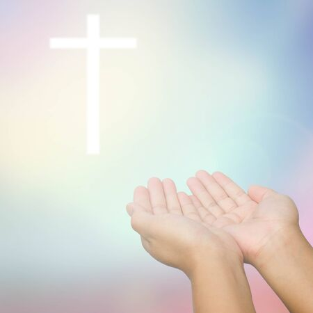 outstretched hand: open hands praying the cross on blur sky background. Stock Photo