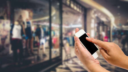 streamlined: Hand holding smartphone on shopping mall