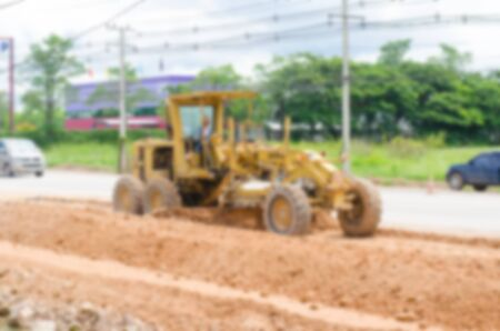 grader: Blurred image motor grader, road construction work Stock Photo