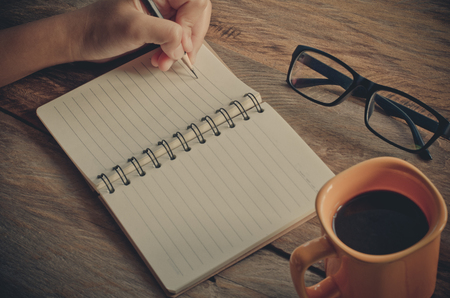 left handed: Hand left writing on notebook and coffee cup on a wooden table. Stock Photo