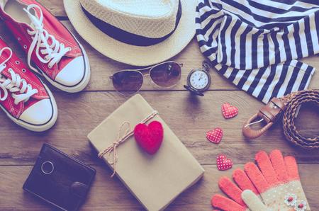 accesorios de vestir para las mujeres y caja de regalo de corazón rojo con el amor en el suelo de madera Foto de archivo